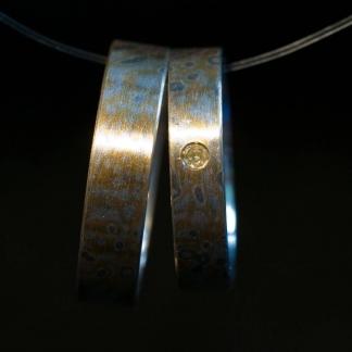 Eheringe aus 925/-Silber, 917/-Gelbgold und 500/-Palladium mit einem hellgelben Brillanten, gearbeitet mit der Mokume-Gane-Technik