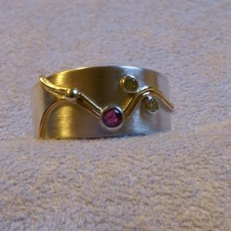 Fingerring mit persönlicher Geschichte aus 925/-Silber und 585/-Gelbgold mit einem Rubin und Brillanten