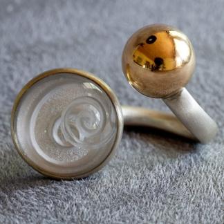Offener Fingerring aus 925/-Silber mit einem Bergkristall mit eingeschliffener Spirale und 750/- Gelbgoldkugel