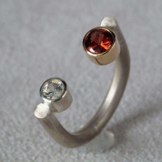 Fingerring aus 925/-Silber und 750/- Gelbgold, mit einem Granat und einem Zirkon