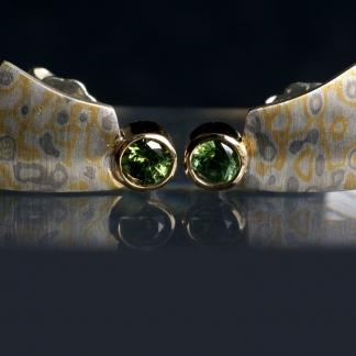 Ohrstecker gefertigt mit der Mokume Gane Technik aus 925/-Silber, 917/-Gold und 500/-Palladium mit grünen runden Zirkonen